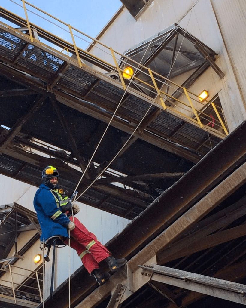 man rappelling down an industrial building