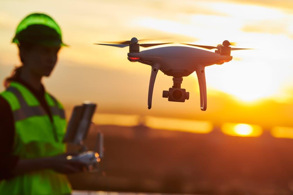 women in hard hat using an industrial drone