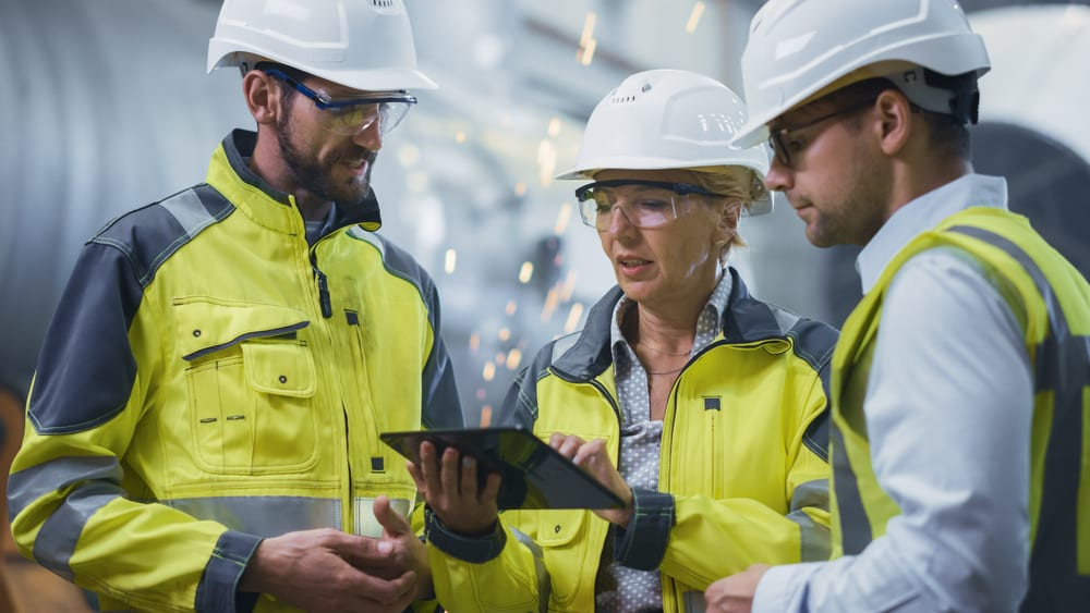 three workplace foremen and women looking at a tablet