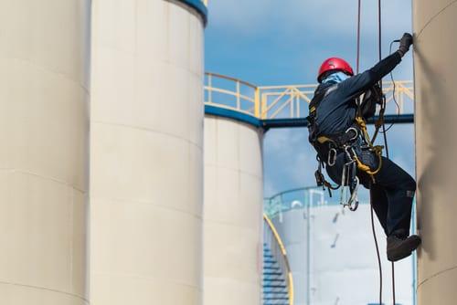 man rappelling down concrete silo