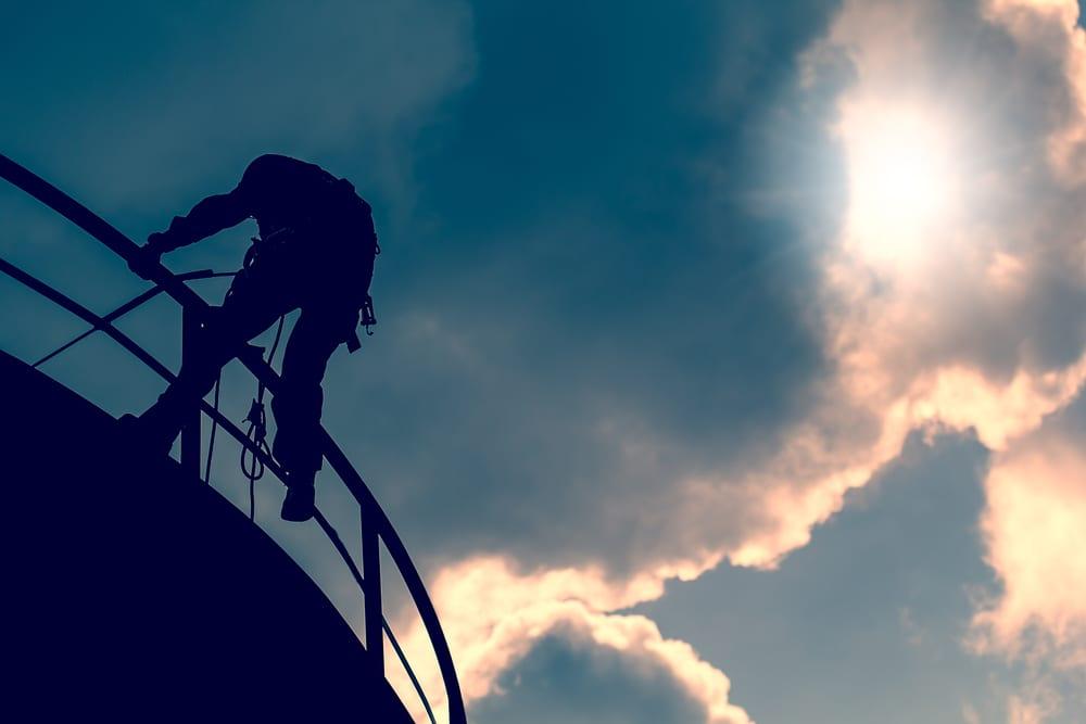 man on top of oil tank