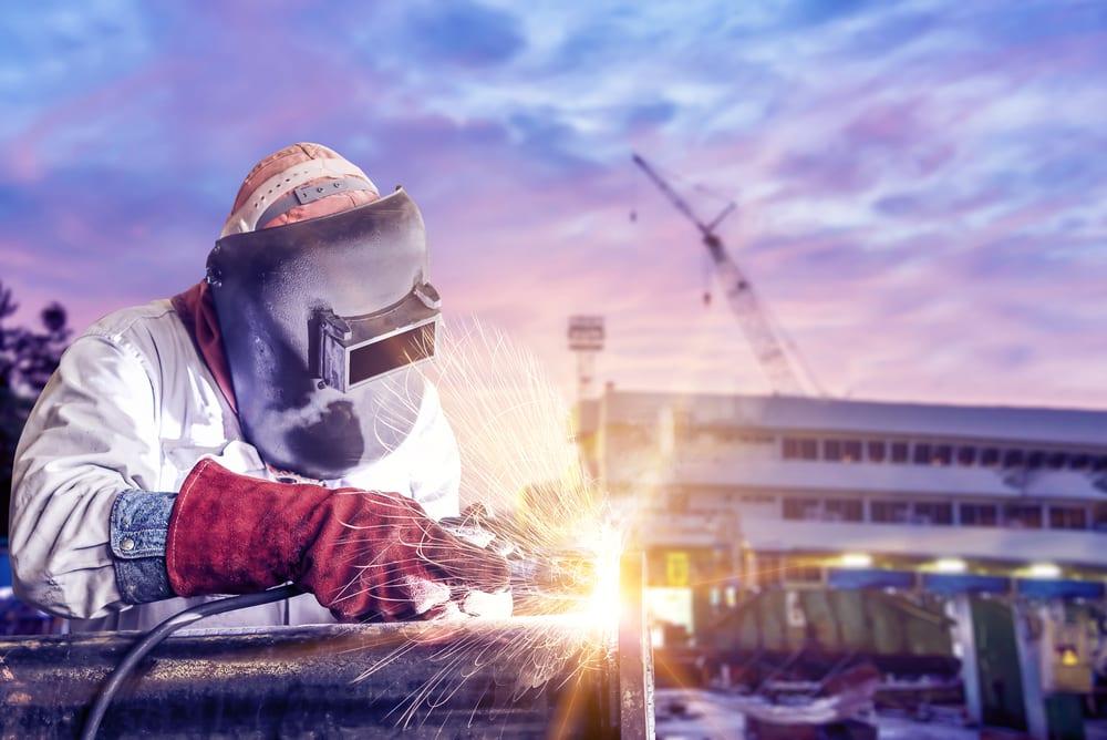 man welding pipe